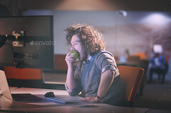 man eating apple in his office - Stock Photo - Images