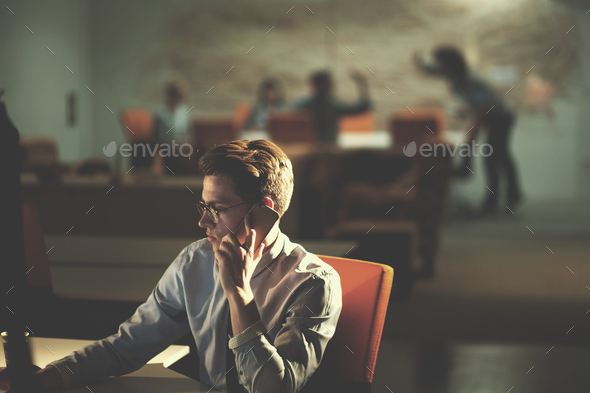 man using mobile phone in dark office - Stock Photo - Images