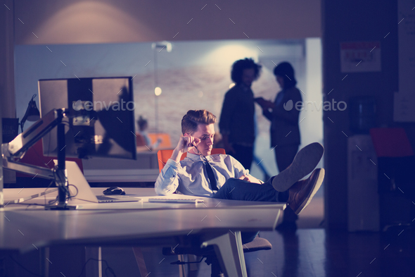 businessman sitting with legs on desk at office - Stock Photo - Images
