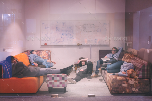 software developers sleeping on sofa in creative startup office - Stock Photo - Images