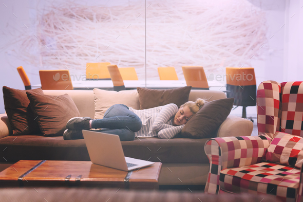 woman sleeping on a sofa  in a creative office - Stock Photo - Images