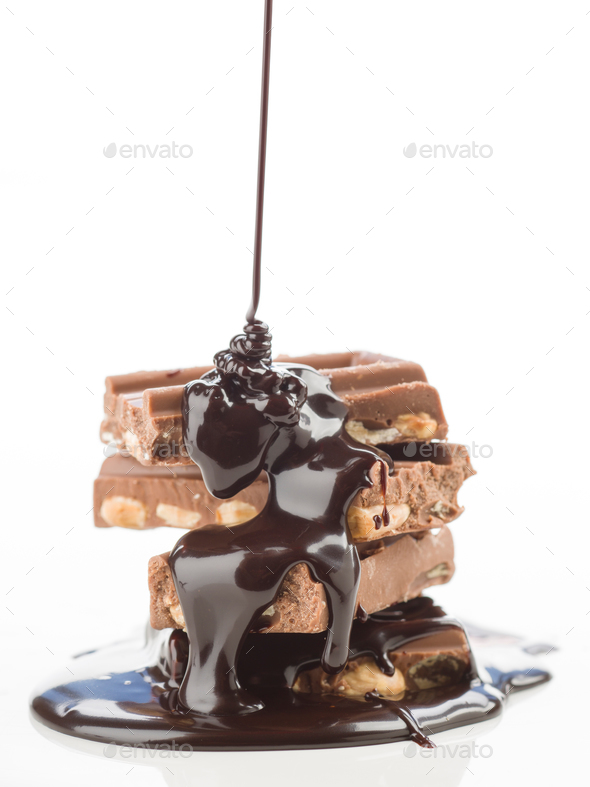 liquid chocolate, falling into group of pieces of chocolate on white - Stock Photo - Images