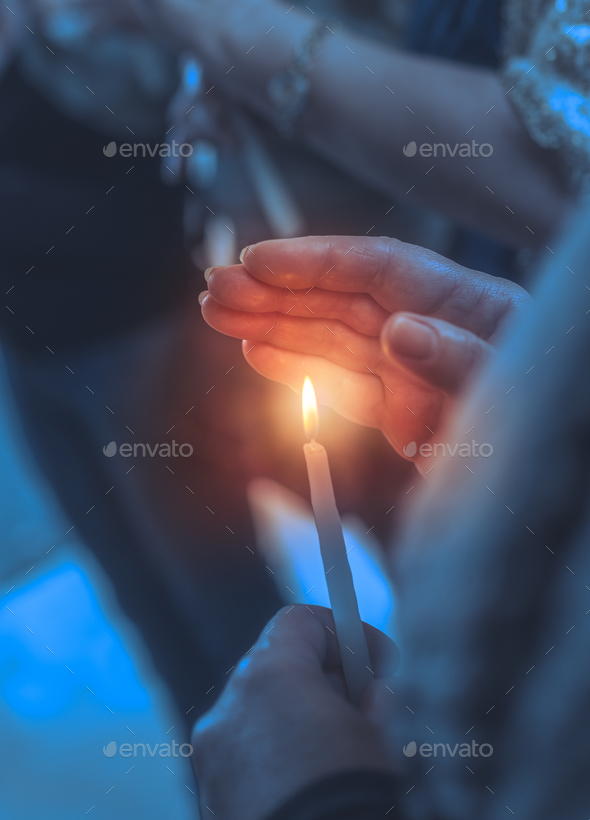 Believer in a church with candle - Stock Photo - Images