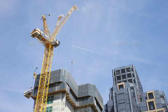 LONDON - MAY, 2017: Crane and modern buildings under construction against blue sky, - Stock Photo - Images