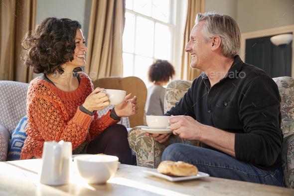 Middle Aged Couple Sitting Around Table In Coffee Shop - Stock Photo - Images