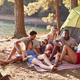 Friends on a camping trip relaxing on a blanket by a lake - PhotoDune Item for Sale