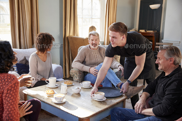 Waiter Serving Group Of Mature Friends In Coffee Shop - Stock Photo - Images