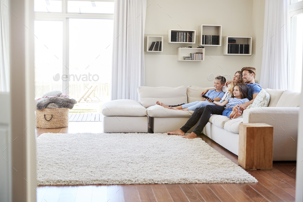 Family Sitting On Sofa At Home Watching Tv Together Stock Photo Images