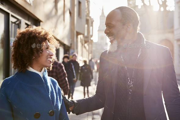 Middle Aged Couple Walking Through City In Fall Together Stock Photo by monkeybusiness
