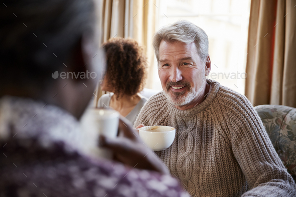 Middle Aged Man Meeting Friends Around Table In Coffee Shop - Stock Photo - Images