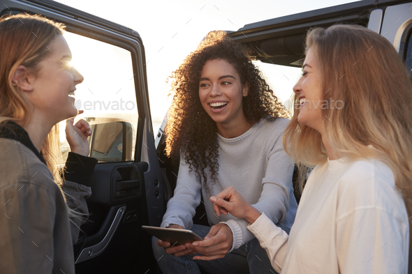 Female friends planning road trip route with tablet computer - Stock Photo - Images