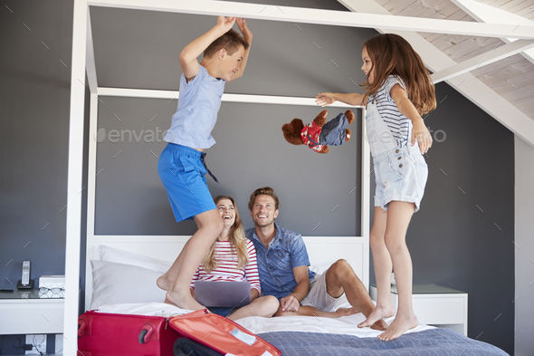 Excited Children Jump On Bed As Parents Pack For Vacation - Stock Photo - Images