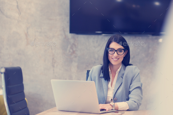 businesswoman using a laptop in startup office - Stock Photo - Images