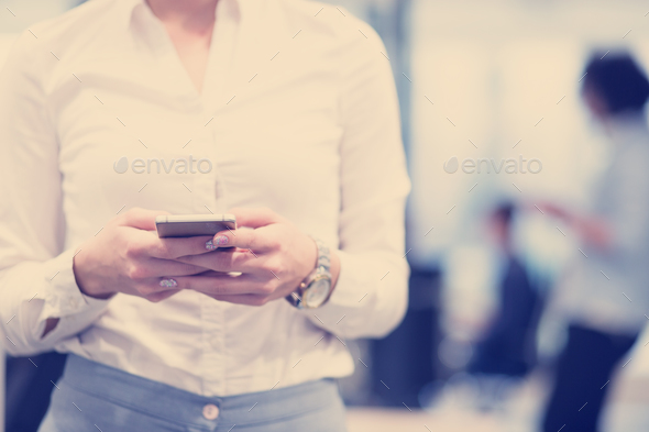 Elegant Woman Using Mobile Phone in startup office building - Stock Photo - Images