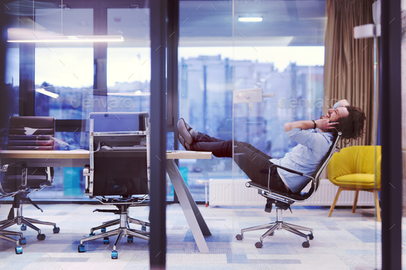 young businessman relaxing at the desk - Stock Photo - Images