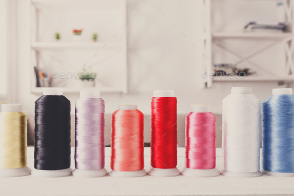 Colorful thread spools on wooden table close up - Stock Photo - Images