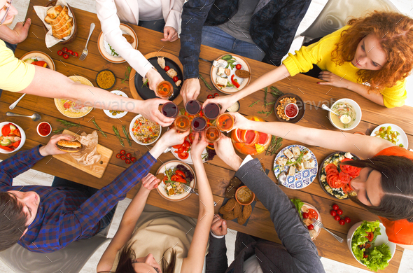 People say cheers clink glasses at festive table dinner party - Stock Photo - Images