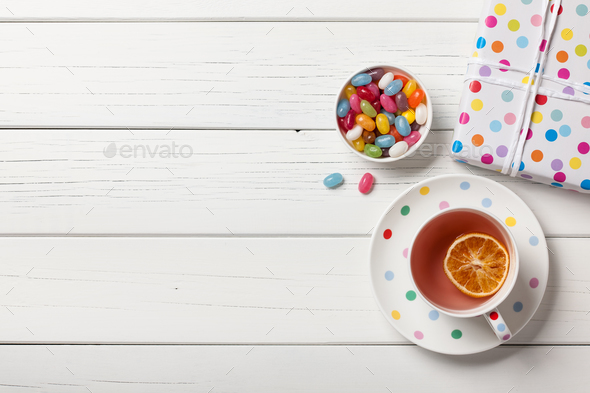 Gift box, cup of tea and colorful candies on white wooden background - Stock Photo - Images