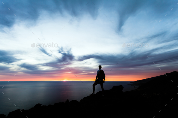 Celebrating or meditating man looking at sunset ocean - Stock Photo - Images