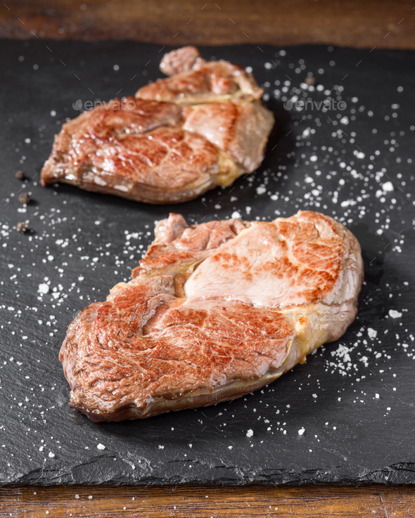 fillets of grilled horse meat on black stone - Stock Photo - Images