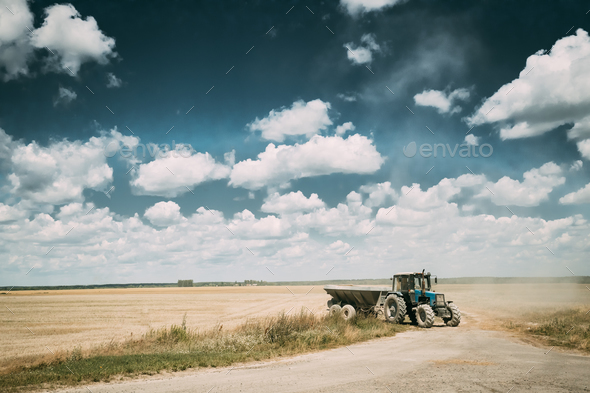 Tractor With Cart In Motion On Country Road In Summer Season. Ag - Stock Photo - Images