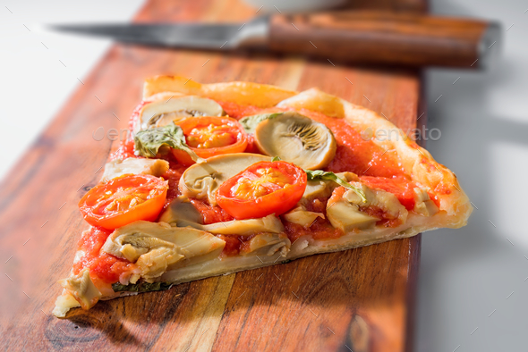 serving of mushroom and tomato pizza served on wooden board - Stock Photo - Images