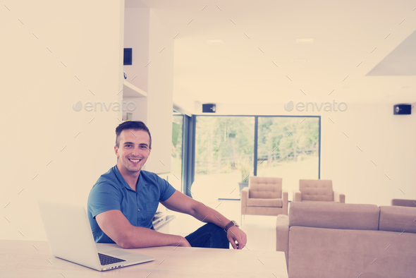 Young man with laptop at home - Stock Photo - Images