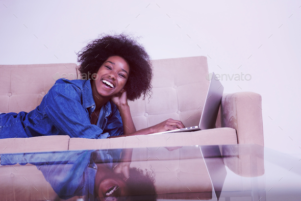 African American woman using laptop on sofa - Stock Photo - Images