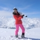 Woman Holding Skis On Her Shoulders, Standing Against The Background Mountains - VideoHive Item for Sale