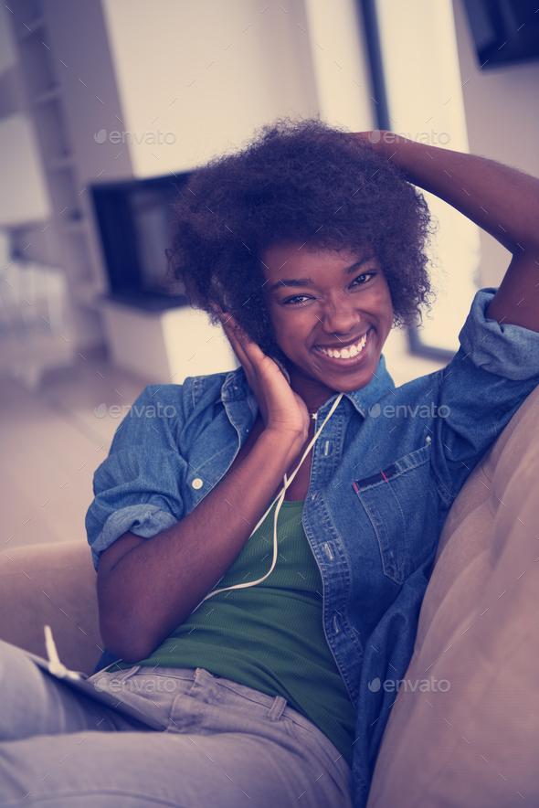 African american woman at home in chair with tablet and head pho - Stock Photo - Images