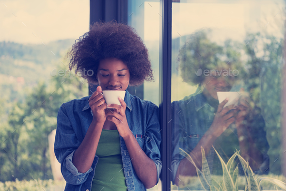 African American woman drinking coffee looking out the window - Stock Photo - Images