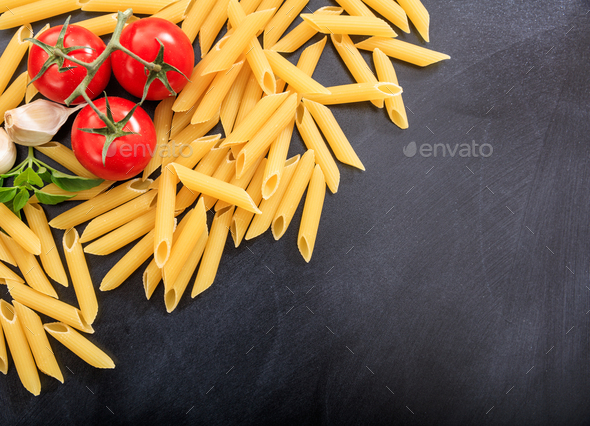 Raw penne pasta on black background - Stock Photo - Images