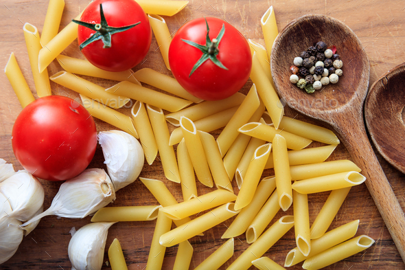 Raw penne pasta with tomatoes and garlic - Stock Photo - Images