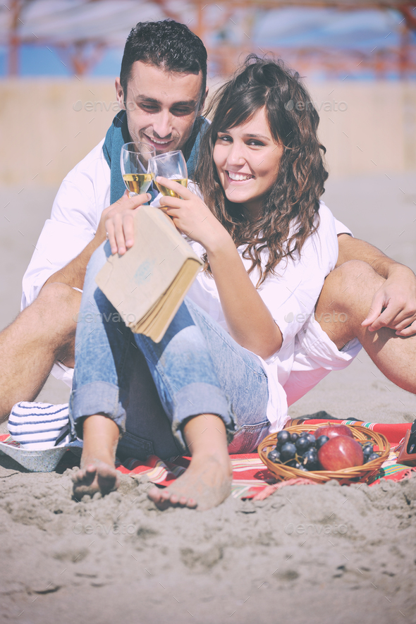 young couple enjoying  picnic on the beach - Stock Photo - Images