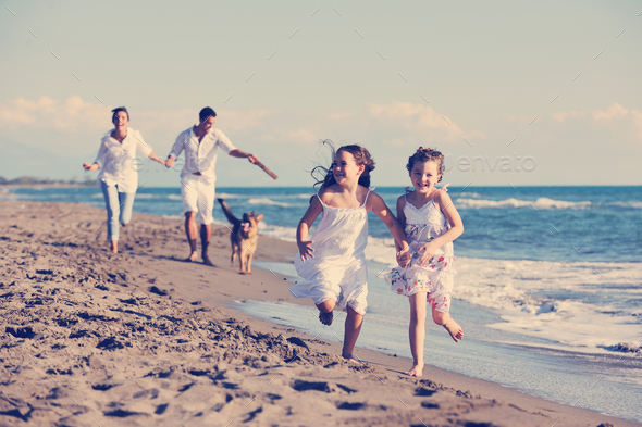 happy family playing with dog on beach - Stock Photo - Images
