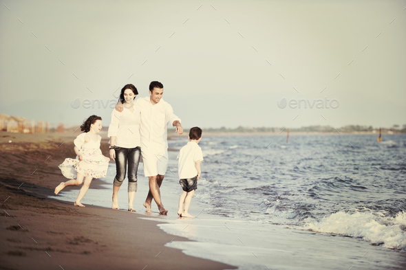 happy young family have fun on beach at sunset - Stock Photo - Images