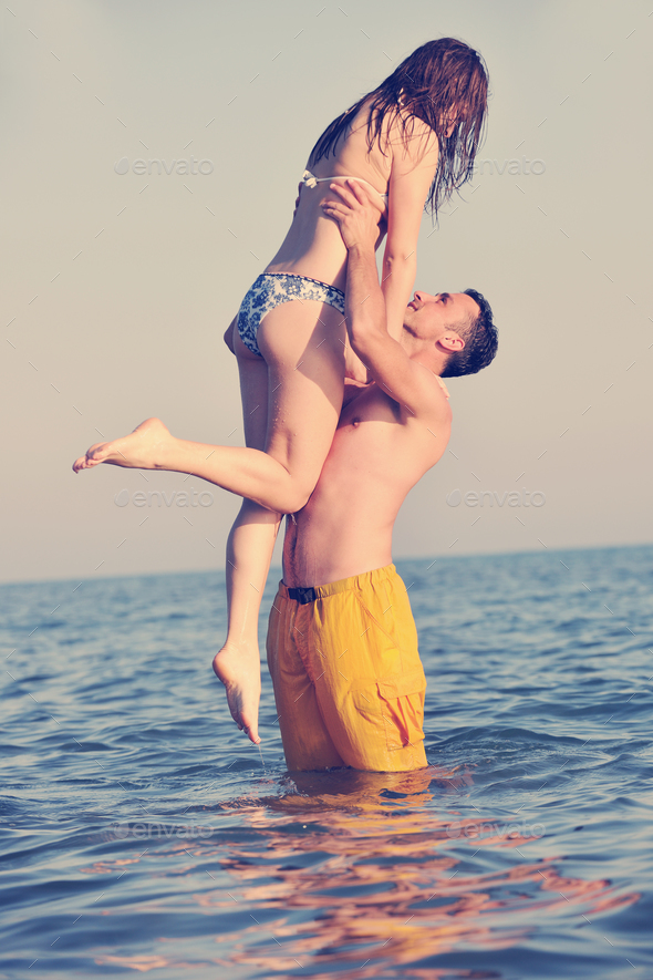 happy young couple have fun on beach - Stock Photo - Images