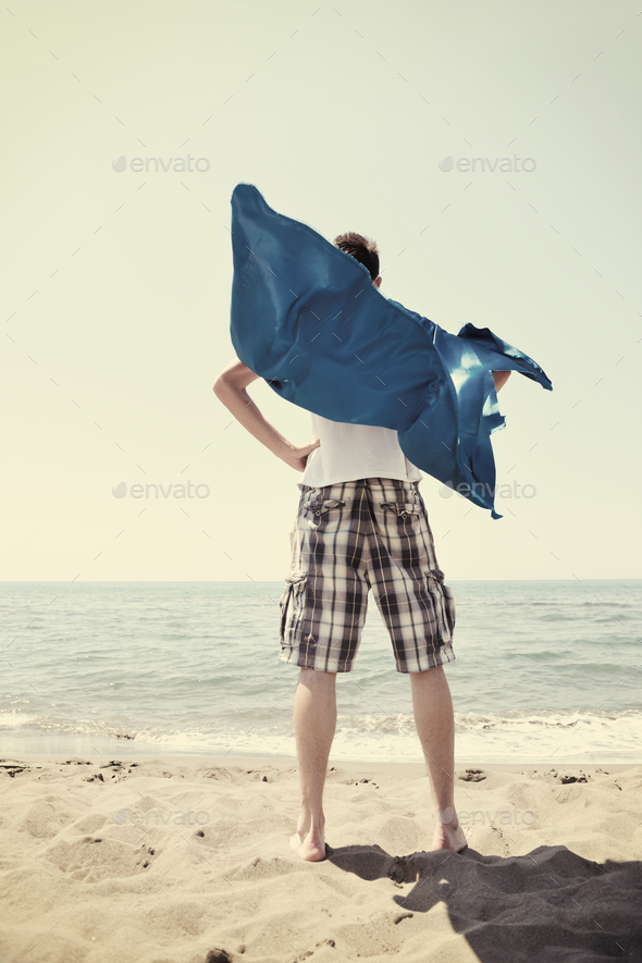 funny superhero standing on beach - Stock Photo - Images