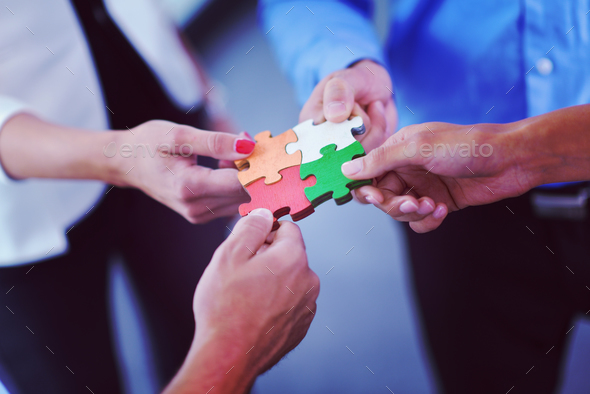 Group of business people assembling jigsaw puzzle - Stock Photo - Images