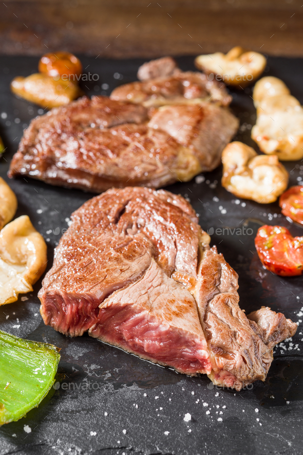 macro shot of half-cooked horse meat fillets on black stone - Stock Photo - Images
