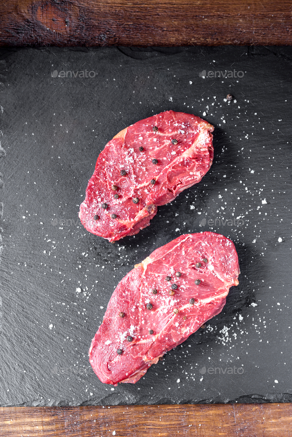 uncooked horse meat steaks on black stone - Stock Photo - Images