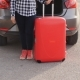 A Young Woman Traveler with a Suitcase Stands near Her Car - VideoHive Item for Sale