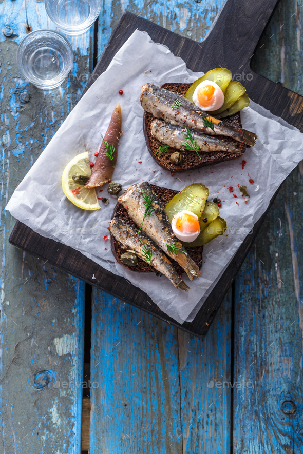 Sandwich with sprats and egg on wooden table, close up - Stock Photo - Images