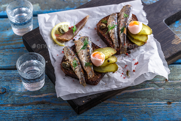 Vodka and a set of sandwiches with sprats on a wooden background. Top view. Copy space - Stock Photo - Images