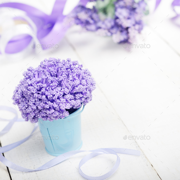 Violet flowers in blue metal bucket on white wooden table - Stock Photo - Images