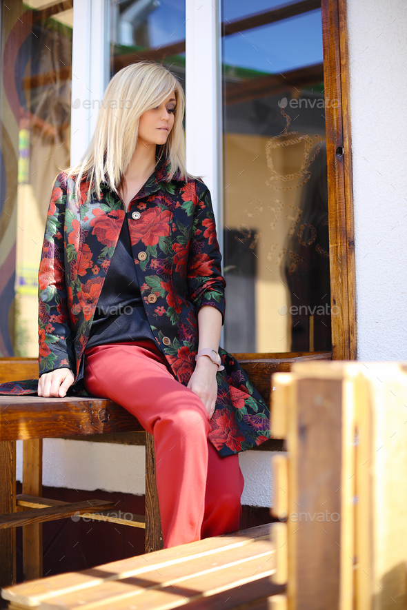 young beautiful stylish woman posing on street in floral printed - Stock Photo - Images