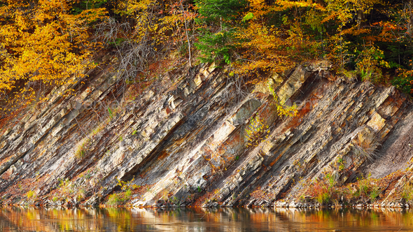 Rocky shore of lake in autumn time - Stock Photo - Images
