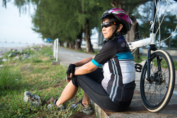 Senior Asian woman riding a bicycle - Stock Photo - Images