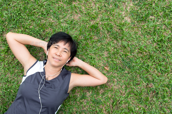 Senior woman laying on the grass - Stock Photo - Images
