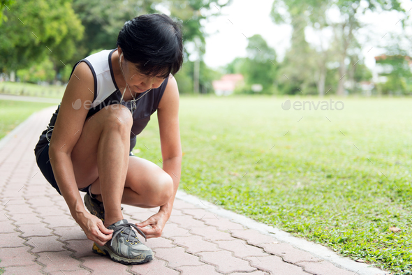 Senior jogger tighten her running shoe laces - Stock Photo - Images